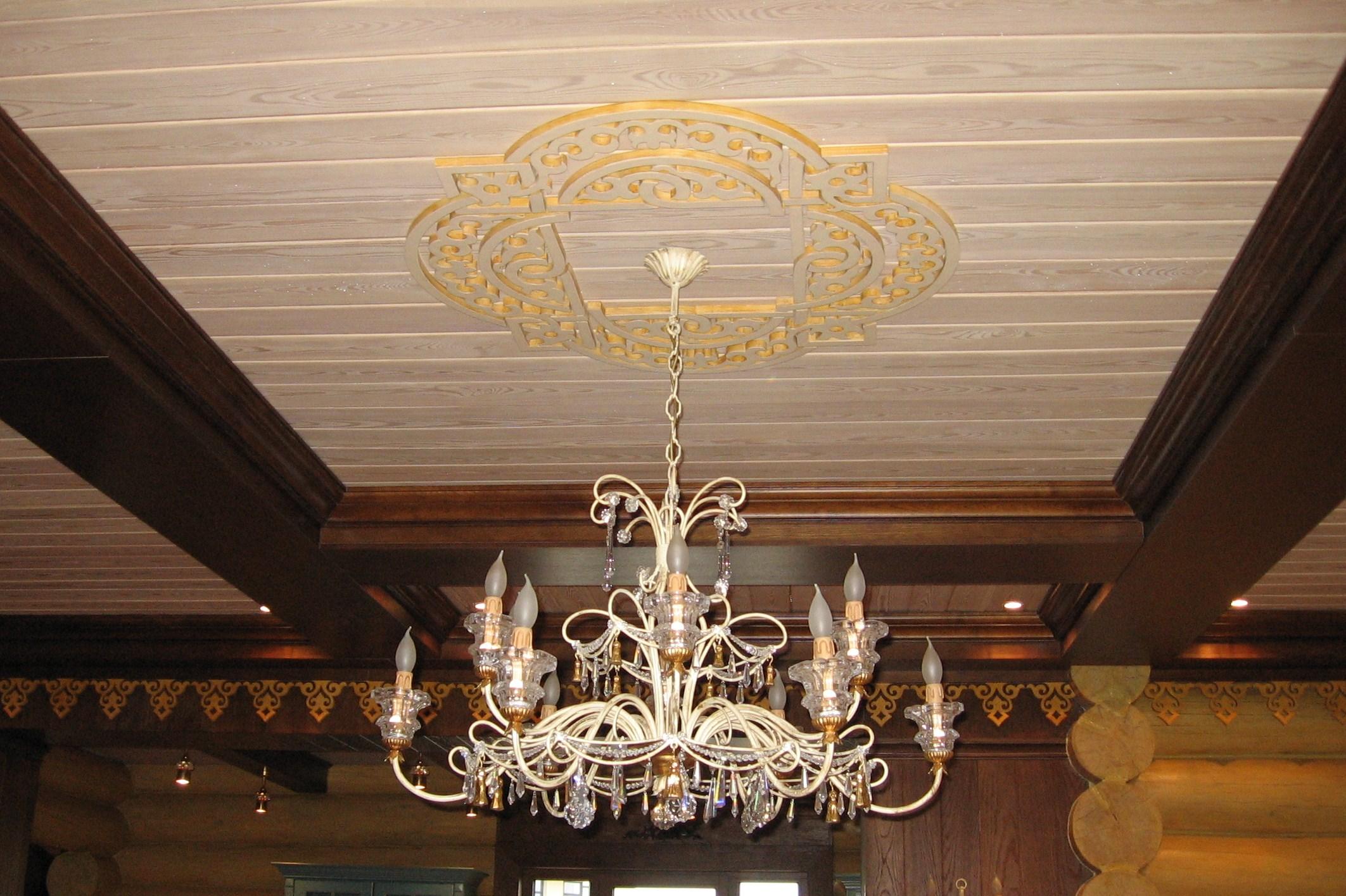 Внутренняя отделка деревянного дома, фрагмент потолка с резным орнаментом