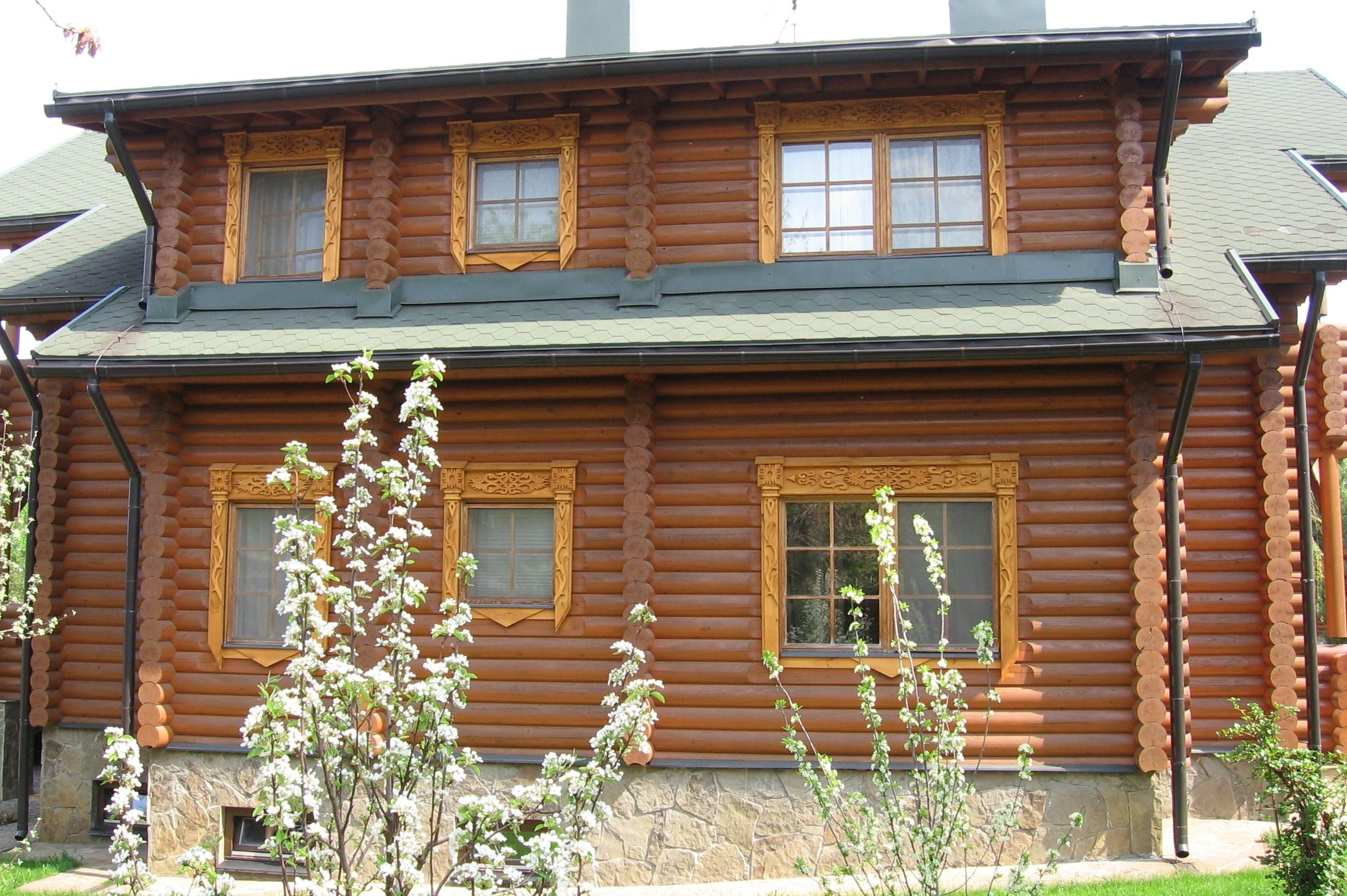 Фасад деревянного дома после установки резных наличников