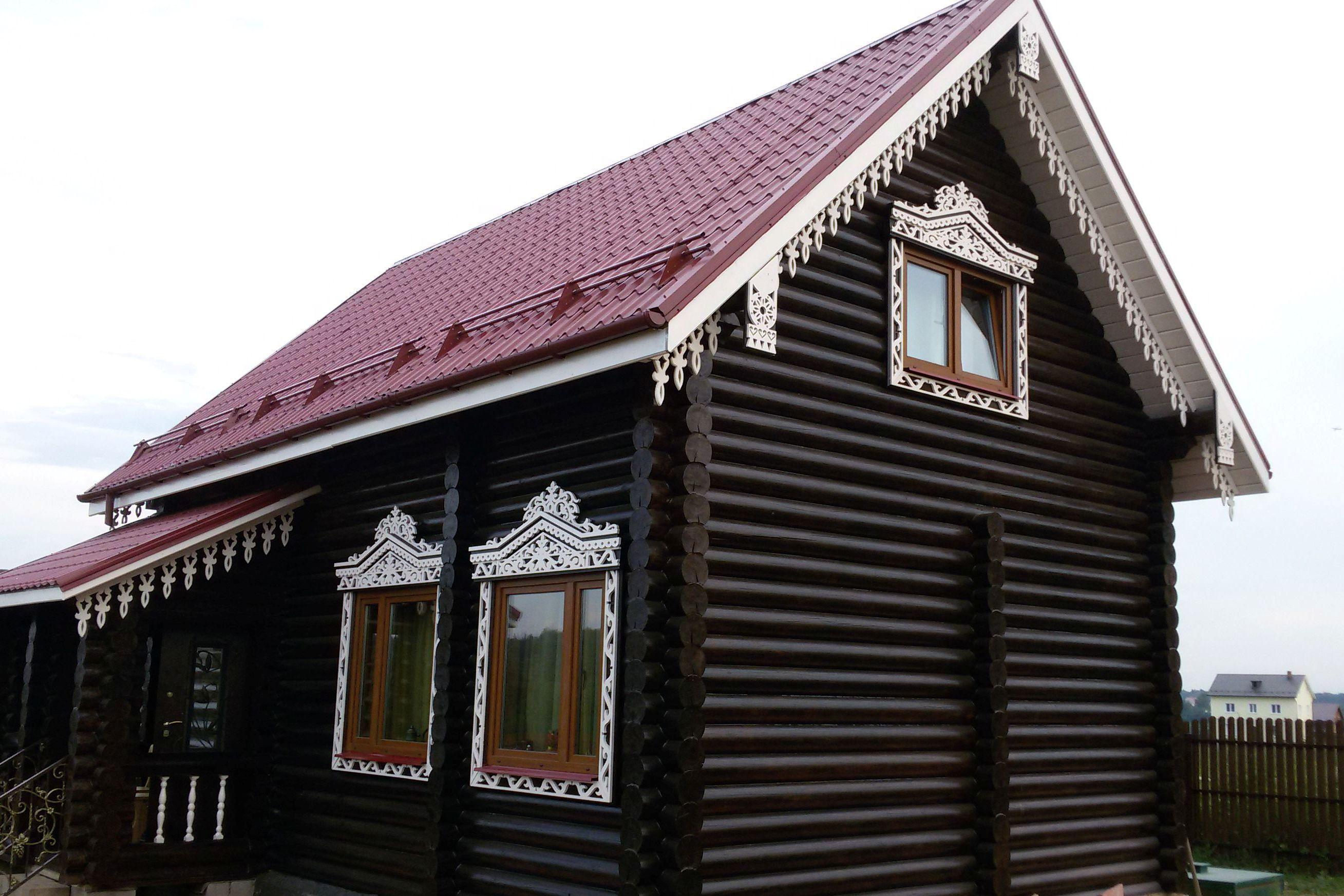 Светлые резные наличники и карнизы на темном фасаде деревянного дома