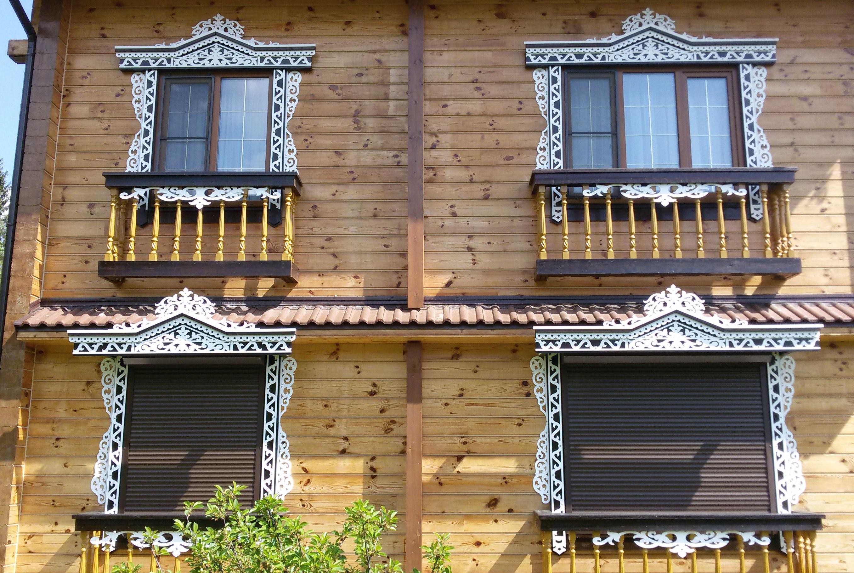 Белые резные наличники и карнизы на фасаде деревянного дома