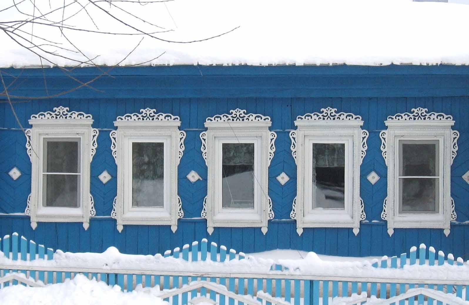 Восстановленный фасад деревенского дома украшенного домовой резьбой