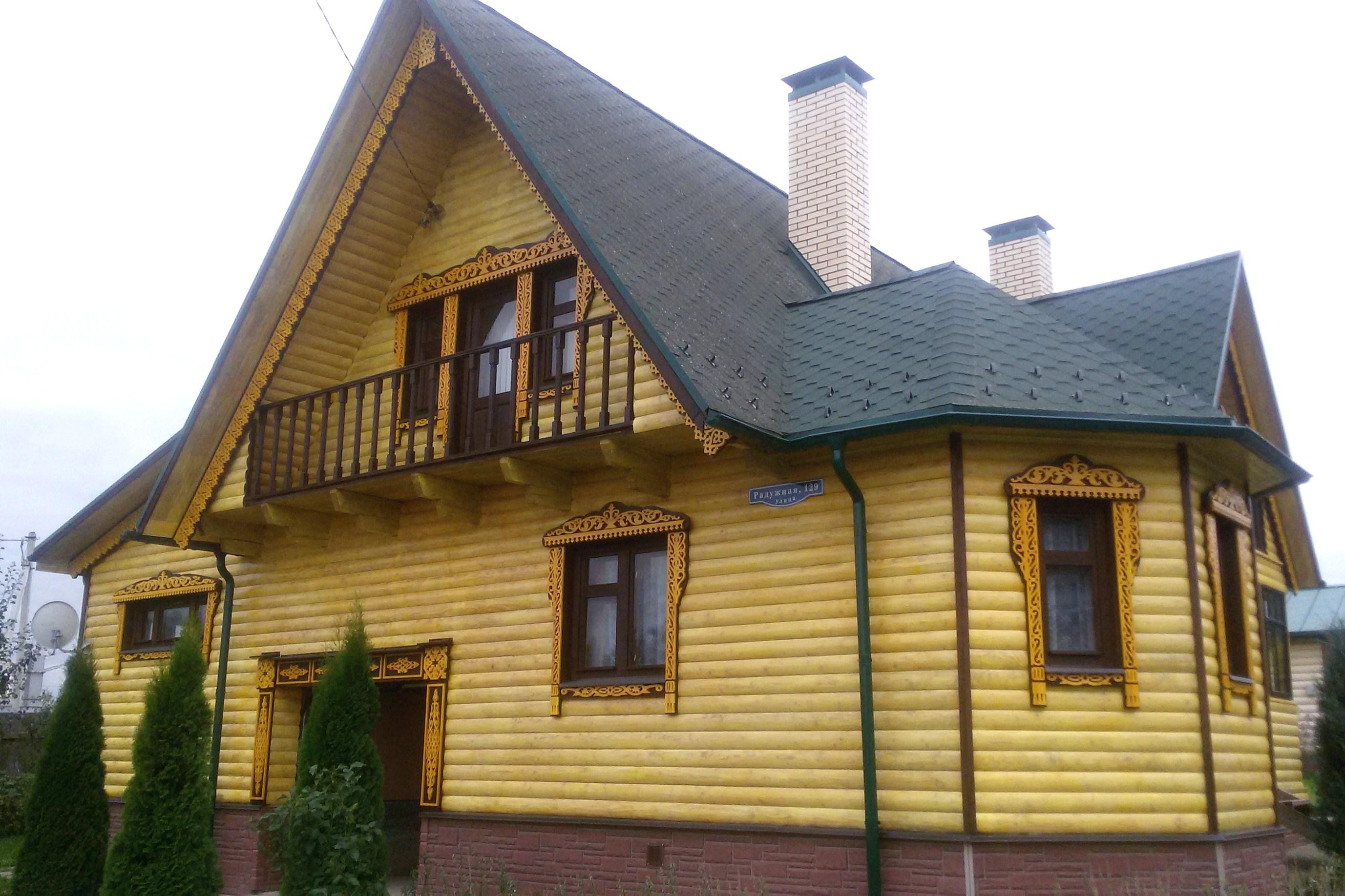 Фасад деревянного дома украшенный резными наличниками и карнизами