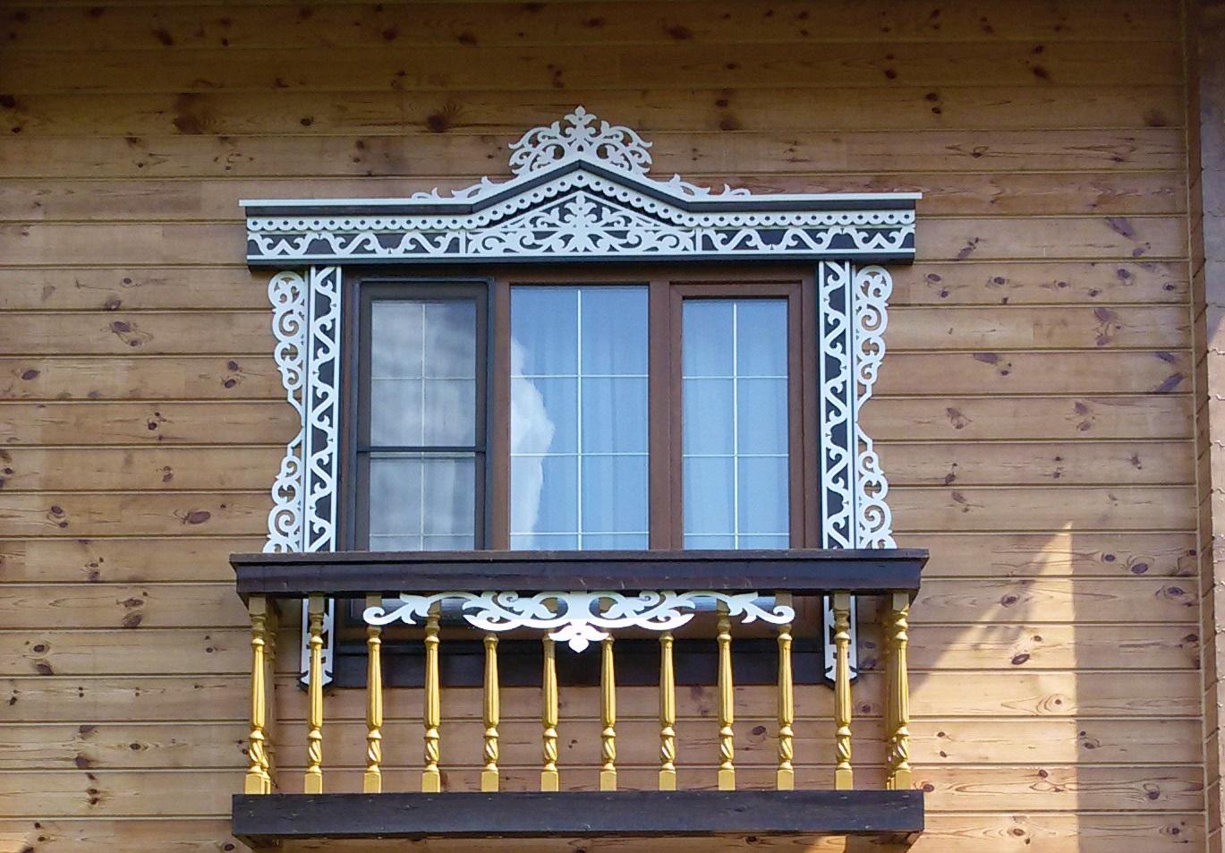 Белый резной наличник на фасаде деревянного дома